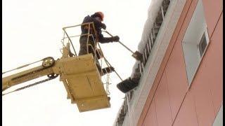 Нефтеюганские коммунальщики чистят крыши жилых домов от сосулек